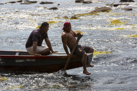 guides: Two Indian native guides at work on wooden traditional canoe in Caroni River at Canaima National Park, Bolivar State. Venezuela, in 2015. Editorial