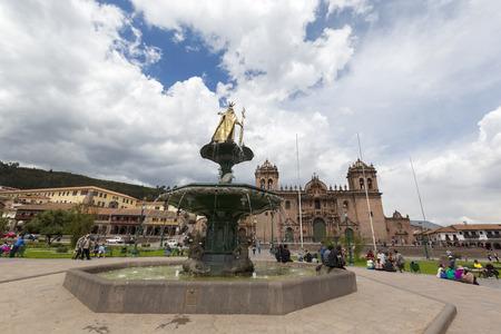 Cusco Main Square Plaza de Armas with the Inca Statue in front of the Iglesia de la Compania with tourists in Cusco, Peru 2015