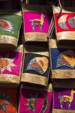 artisanry: Handmade colored Woolen and leather bags for sale at the tourist craft market in Cusco. Peru Stock Photo