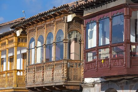 plaza de armas: Colored colonial rustic wooden carved balconies on Plaza de Armas in the historic center of Cusco. Peru Stock Photo