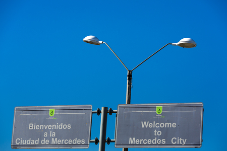 bidirectional: Welcome to Mercedes City road sign with vintage street light and clear blue sky at the border entre Argentina and Uruguay. 2014