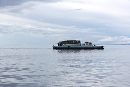 transported: Being white bus transported on wooden ferry over the Strait of Tiquina Lake Titicaca at in San Pablo de Tiquina, Bolivia 2015
