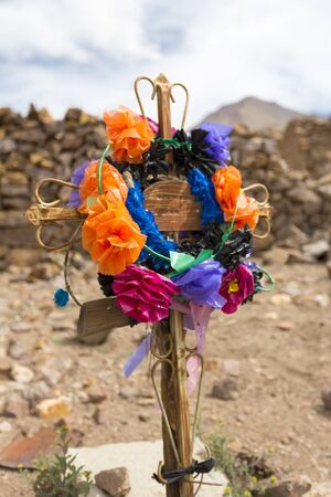 tumb: Details of wooden old christian religious cross with colored flowers on tumb in abandoned and decaying church in San Antonio ghost village at the footstep of San Antonio volcano in the Bolivian altiplano.