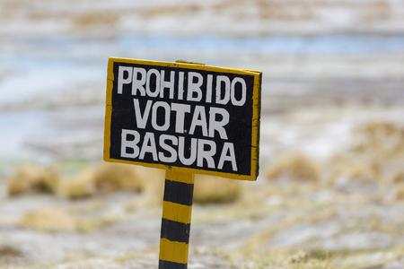 botar basura: Poste de muestra de madera diciendo prohibido Votar basura escrito en español (Tirar basura prohibido) en las Termas de Polques. Bolivia