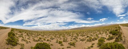 4x4: Panorama of 4x4 track in desert in the mountains of Eduardo Avaroa Andean Fauna National Reserve with cloudy blue sky, Bolivia