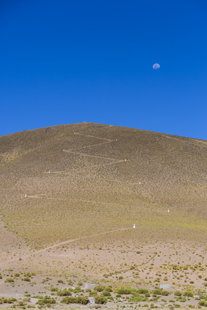 avaroa: Way up in zigzag to the mountain at 4500 m. with the moon and clear blue sky in Eduardo Avaroa Andean Fauna National Reserve, Bolivia