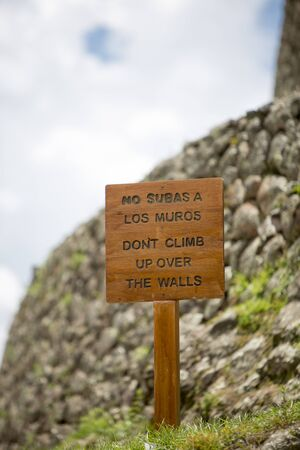 wooden trail sign: PISAC, PERU, JANUARY 15: Closeup on wooden sign with No subas a los muros (Dont climb up over the walls) written in Spanish at the Pisac Inca Ruins near Cusco. Peru 2015