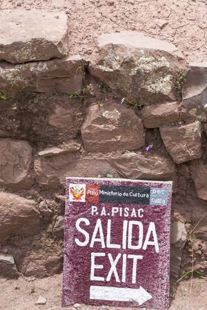 wooden trail sign: Closeup on wooden sign with Exit Salida written in Spanish at the Pisac Inca Ruins near Cusco. Peru 2015