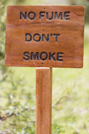fume: Closeup on rustic old wooden sign with No fume (Dont smoke) written in Spanish isolated with blurred background Stock Photo