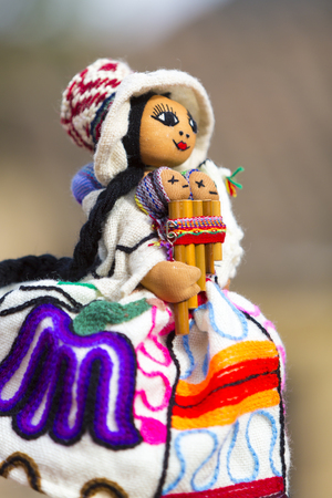 playing the market: Hand made colored puppet in Cusco market. Women face with traditional Peruvian Quecha clothes and Peruvian flute, isolated on blurred background. Peru 2015 (Selective focus) Stock Photo