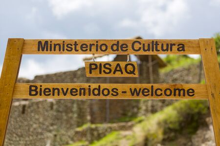 inca ruins: Closeup on welcome wooden sign written in Spanish and English at the Pisac Inca Ruins near Cusco. Peru 2015 Stock Photo
