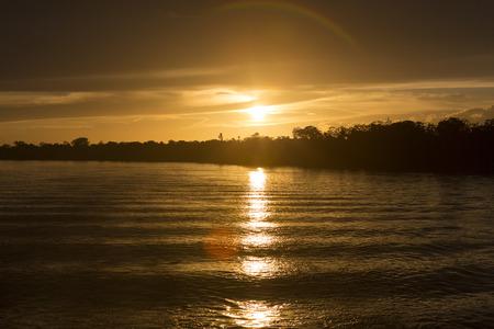 espejo: Maravillosa puesta del sol anaranjada amarilla en el r�o Amazonas, con las siluetas de los �rboles. Estado de Amazonas, Brasil