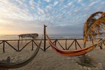 Mit Blick auf gemütlichen Stroh Hängematten auf einem tropischen weißen Strand mit Sonnenuntergang Licht, Punta Sal in der Nähe von Mancora in Peru. Standard-Bild - 50270878