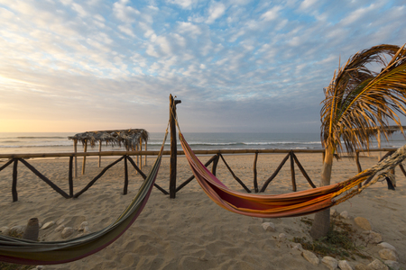 hammock: View of cozy straw hammocks on a tropical white beach with sunset light, Punta Sal near Mancora in Peru.