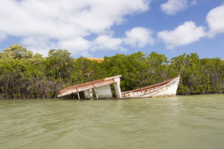 sunk: Old wooden boat wreck sinking in the ocean near Punta Gallinas in La Guajira with clear blue sky, Colombia