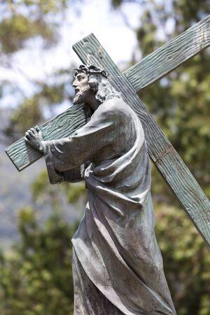 carrying the cross: Antique statue of Christ carrying the Christian cross part of the Basilica of the Senor de Monserrate with blue sky, designed by architect Arturo Jaramillo Concha in 1925. Located on the Cerro de Monserrate in Bogota Colombia.