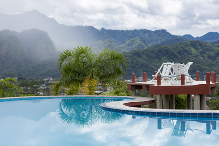 amazon rain forest: Long chairs standing by the swimming pool with tropical mountains in the background in Rurrenabaque, the gateway to the Bolivian Amazon rain forest. Bolivia 2015