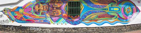 window graffiti: Colorful graffiti of Inca colored signs painted on a wall in the historic district of Bogota with vintage wooden window. La Candelaria, Colombia 2015