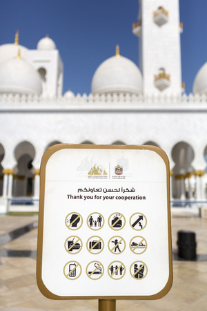 dictating: White signboard dictating the rules and behaviors at the Abu Dhabi Sheikh Zayed White Grand Mosque, United Emirates Arab