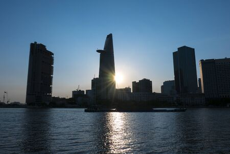 highriser: Silhouette of Bitexco tower and Ho Chi Minh (Saigon) city skyline in front of the river. Vietnam Editorial