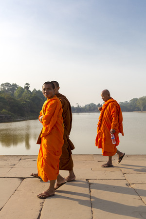 sandal tree: Three smiling Cambodian monks dressed in orange and walking Toward Angkor Wat temple with the pond in the background. UNESCO heritage site, Cambodia 2016