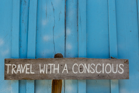 conscious: Wooden sign saying to travel with a conscious wooden on blue  wall background. Stock Photo