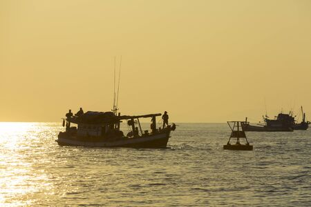 fishingboats: Orange sunset with ocean view and silhouettes of fishing-boats in the bay of Koh Rong Island near Sihanoukville, Cambodia. South East Asia