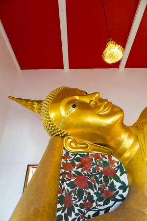 3rd ancient: Huge golden Buddha with white and red background inside a Thai temple, Bangkok, Thailand. Low angle view. Editorial