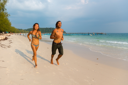 spanish style: Asian woman and Spanish style young man running on the beach in Koh Rong Island near Sihanoukville, Cambodia. South East Asia 2016 Editorial