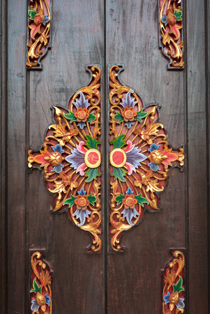 wood carvings: Traditional colorful Balinese style carved door, made of wood, in Ubud, Bali, Indonesia. Stock Photo