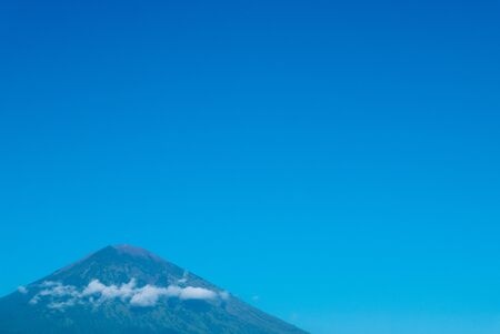 dominating: The volcano Gunung Agung dominating the horizon taken from Amed against a clear blue sky, a little fishing village located on the east coast of Bali, Indonesia.