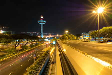 Singapore Internationl Changi Airport at night with air traffic control tower and trails of lights.