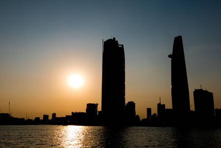 highriser: Silhouette of Bitexco tower and Ho Chi Minh (Saigon) city skyline in front of the river. Vietnam Stock Photo