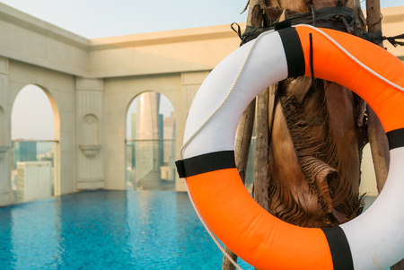 life buoy: Colored life buoy with blue swimming pool site location is the top of a luxury residential condominium in Saigon with the city aerial view in the background. Vietnam 2016 Stock Photo