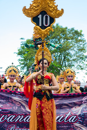 negara: Balinese woman holding a wooden stick with Village number During the New Year Nyepi religious ceremony in the street of Negara - Bali, Indonesia in 2016