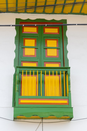 balcony window: Colorful green and yellow window and balcony in traditional colonial Salento white house. Colombia. Stock Photo
