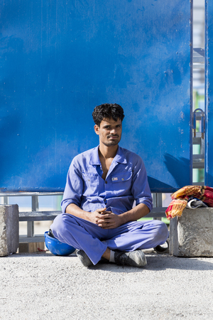 exploitation: Portrait of a young Indian worker sitting in front of a construction site in Dubai. Theme of exploitation of Indian Workers in Dubai. UAE 2016 Editorial