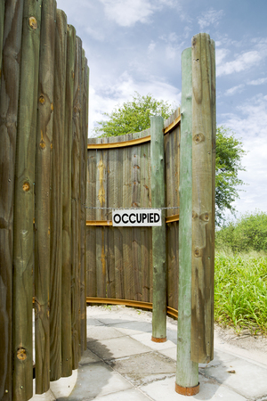 occupied: Details of outdoor toilet in the Central Kalahari Game Reserve in Botswana with occupied restroom sign.