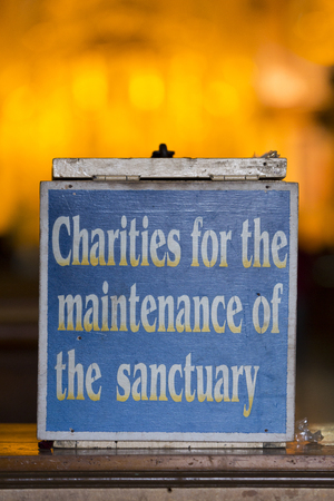 Charity information sign board inside the Iglesia and sanctuary El Jordan with defocussed background in Otavalo. Ecuador 2015.. Stock Photo