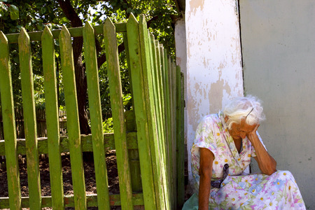 Tired old unidentified woman sitting outside in front of a green fence in Crimea, Ukraine