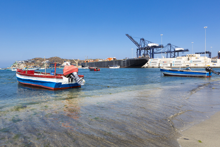 marta: Boat anchored to the shore of Santa Marta, in La Guajira with the harbor and the huge cranes in the background. Colombia 2014