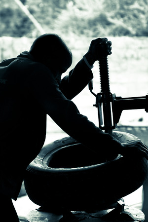 traction engine: Silhouette of a young mechanic working on a tyre at an auto shop in Namibia. Duo toned