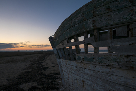 ship wreck: Beautiful sunset and wooden shipwreck standing on the beach taken from the Island of Arz in Brittany (Morbihan), France.