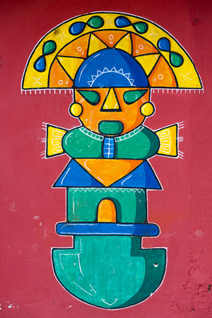 Vintage colored stylized Maya graffiti painted by unknown artist on vintage red wall in Banos. Ecuador 2015 Stock Photo