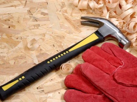 Hammer and gloves over plywood photo