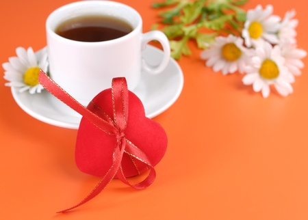 Red heart and cup over orange background photo