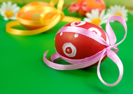 Easter eggs with chamomiles over green background photo