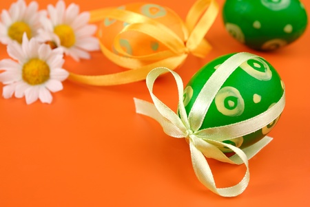 Easter eggs with chamomiles over orange background photo