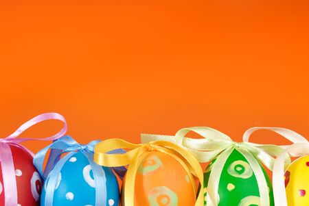 Easter eggs with bows over orange background