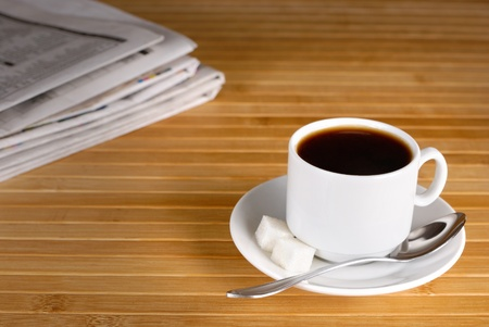 Cup of black coffee on the wooden table and newspaper aside photo